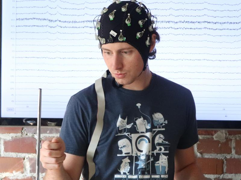 A student plays a theramin while wearing a skullcap to measure brainwaves.
