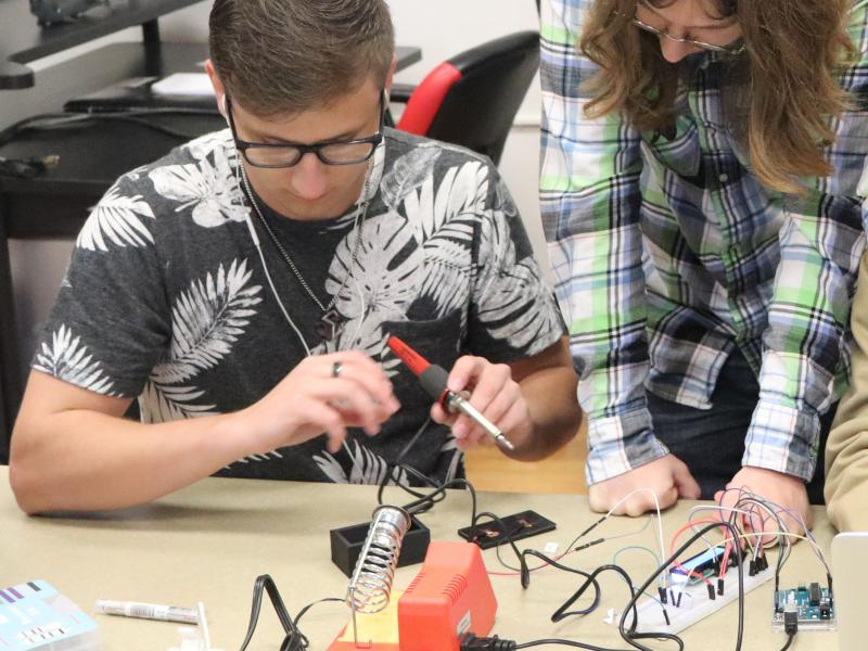 Students working on a research project with a soldering iron.
