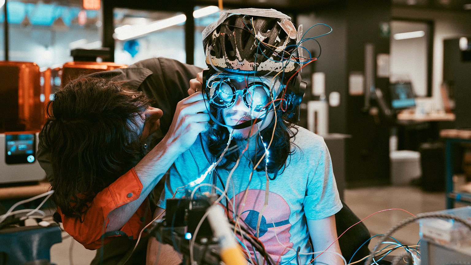 Two hackathon competitors work on a helmet and goggles that create music.