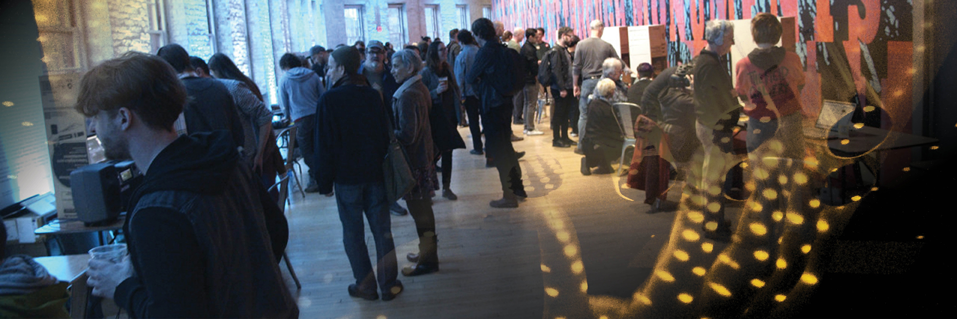 A crowd browses a gallery of different music technology projects.