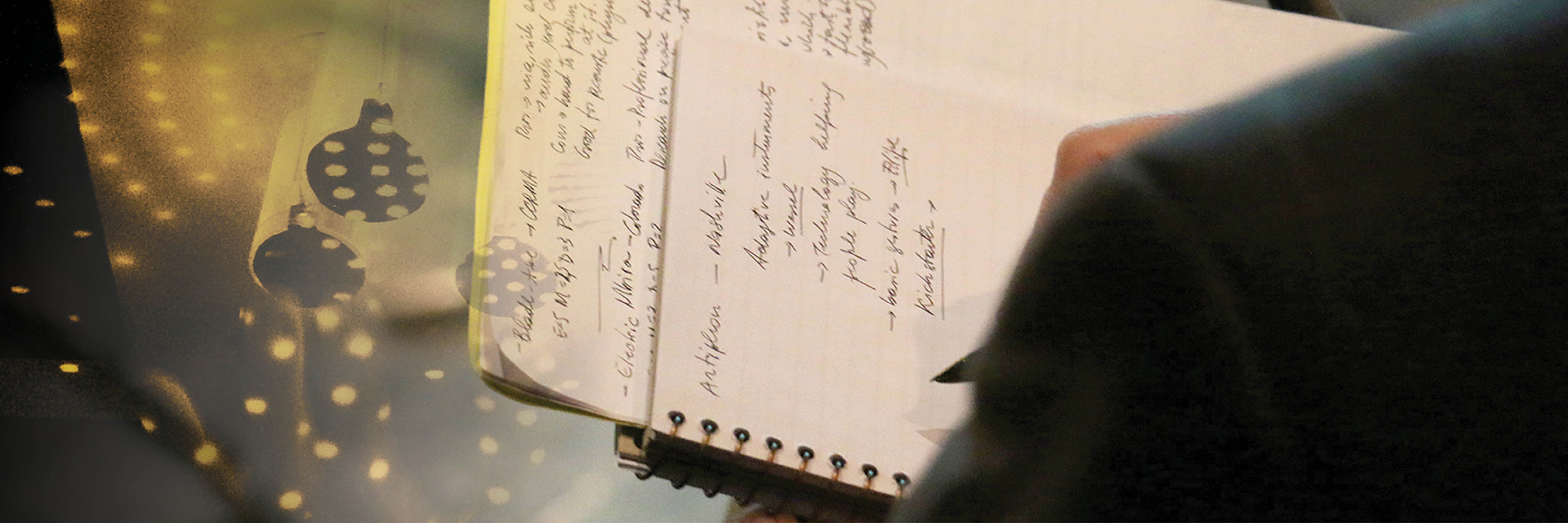 A photo of a Guthman judge's note pad, taken from behind his shoulder as he writes.