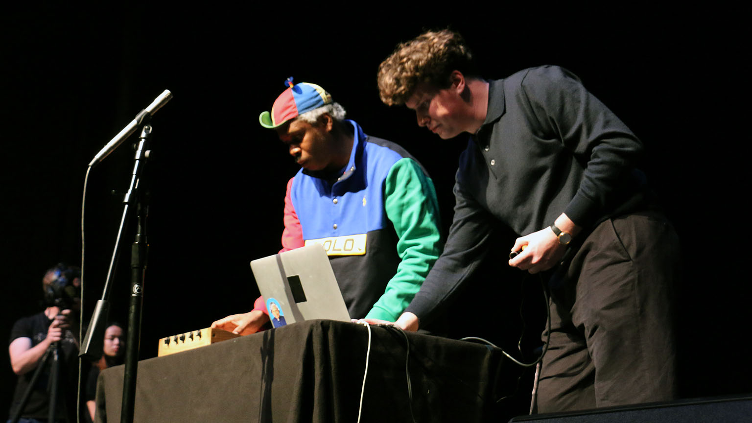Two men playing electronic instruments on stage, adjusting the sound with a laptop in front of them.