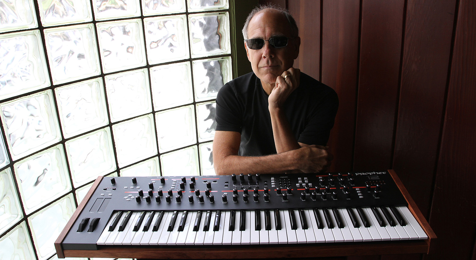 Dave Smith posing by a MIDI keyboard in front of a large window.