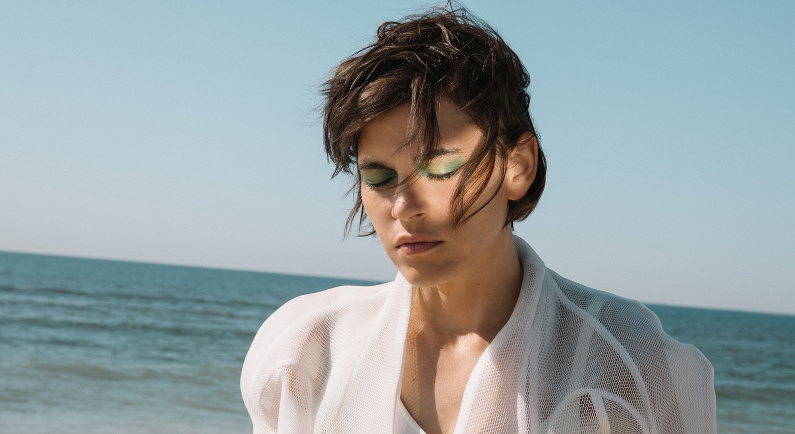 Kaki King standing at a beach with her eyes closed, with a light shining on her face.