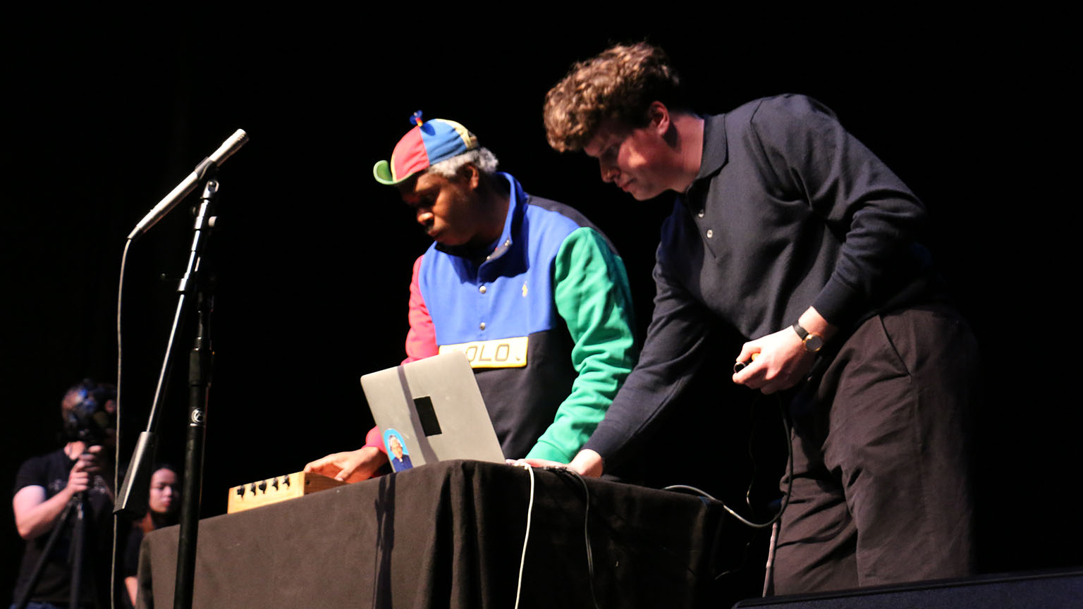 Two men playing a laptop and box instrument on stage.