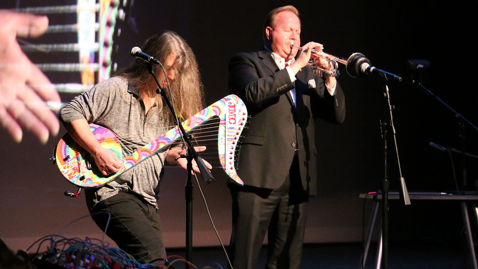 One man playing a trumpet, while another man plays a harp/guitar hybrid with a tie dye design.