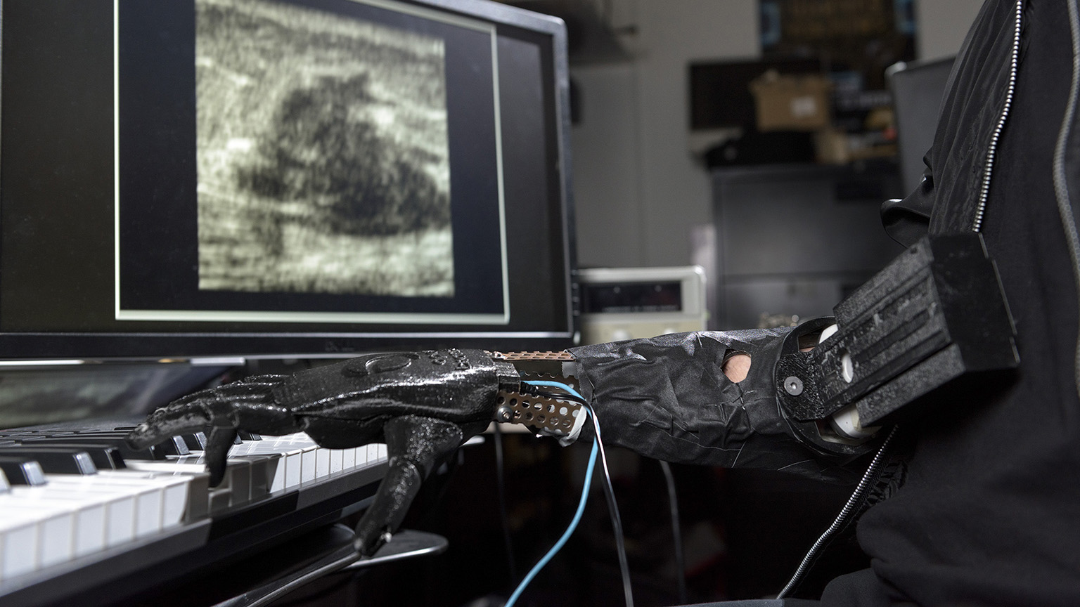 A robotic hand playing music on a piano with a monitor in the background.