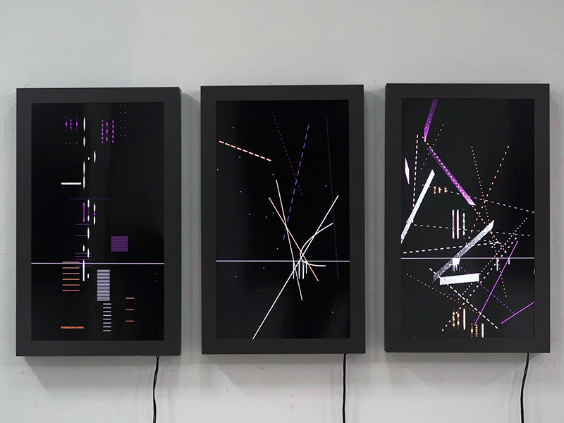 Three rectangular screens with electronic patterns dancing on them.