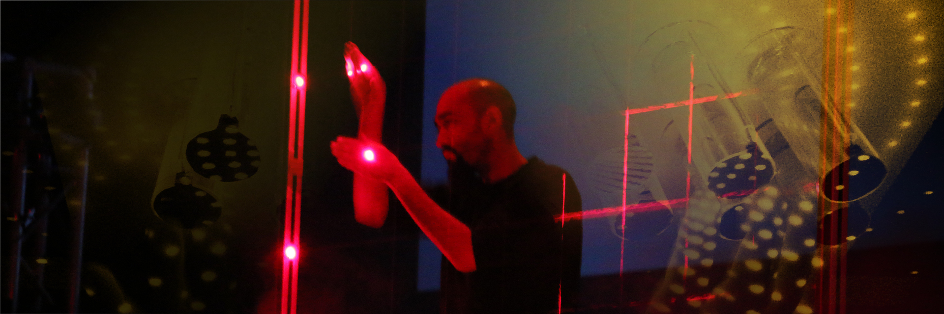 A man playing a set of criss-crossing red lasers within a square frame like a stringed instrument.